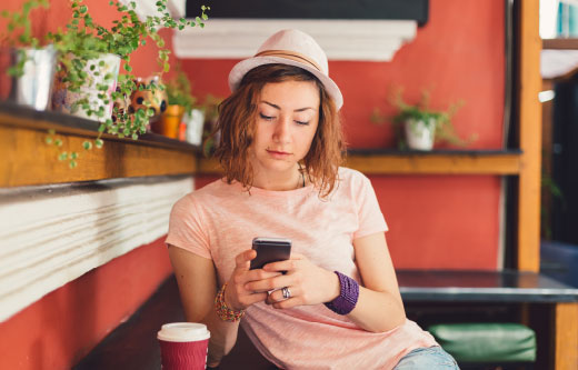 Young woman using her mobile phone in a cafe