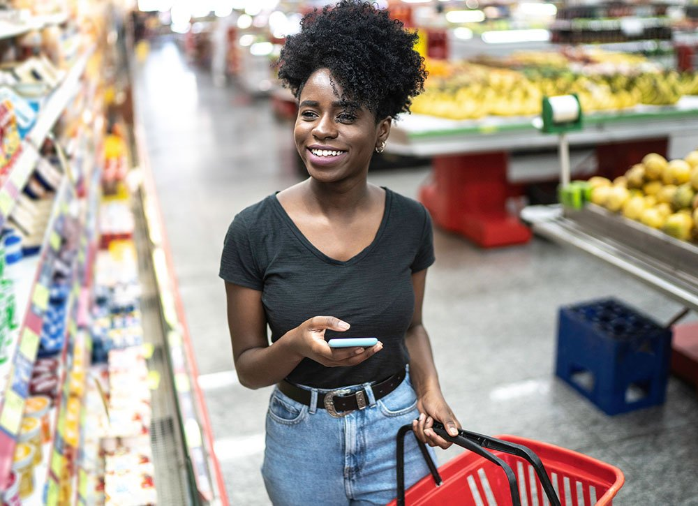 Young woman using mobile phone and choosing product in supermarket